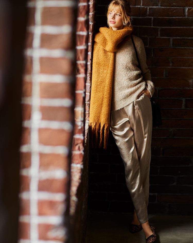 アルパカ混ニットの素朴さと、都会的なサテン素材のコントラストが、ワントーンの着こなしにメリハリをつける。